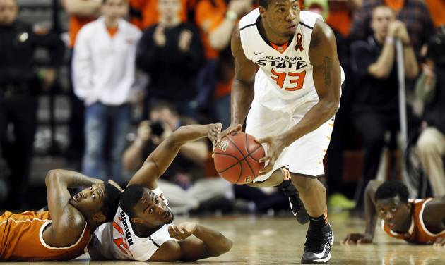 Oklahoma State's Marcus Smart (33) picks up a loose ball in front of Texas' Julien Lewis (14), left, Oklahoma State's Markel Brown (22), middle, and Texas' Myck Kabongo (12) during a men's college basketball game between Oklahoma State University (OSU) and the University of Texas at Gallagher-Iba Arena in Stillwater, Okla., Saturday, March 2, 2013. OSU won, 78-65. Photo by Nate Billings, The Oklahoman