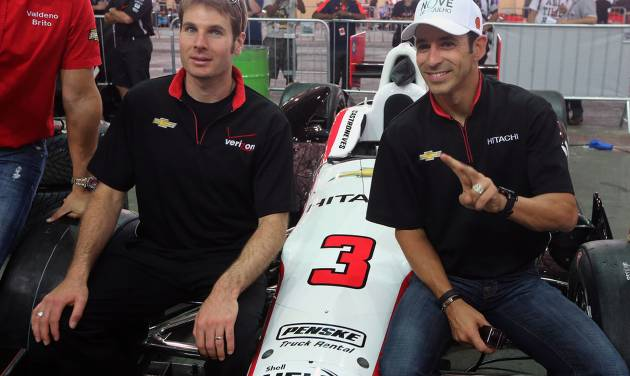 IndyCar drivers Will Power, of Australia, left, and Helio Castroneves, of Brazil, pose for pictures as they sit on Castronves' car in the garage area at the race track in Sao Paulo, Brazil, Friday, May 3, 2013. Brazil will host the 4th race of the Indy Car season on May 5. (AP Photo/Andre Penner)