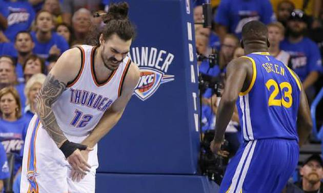 Steven Adams doubles over in pain after being kicked in the groin region by Draymond Green during...