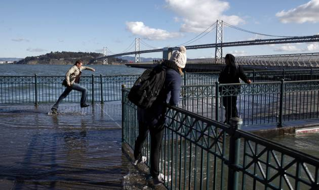 Pedestrians cannot resist getting close to Thursday's king's tide cresting along the San Francisco Embarcadero on Thursday, Dec. 13, 2012. The tide measured 7.2 at the Golden Gate and was the highest of the year. The king tides are expected to peak during the next several days, with surges over 9 feet in some areas. The phenomenon is caused by a unique alignment of the sun, moon and earth.  (AP Photo/Bay Area News Group, Karl Mondon)  MAGS OUT; NO SALES