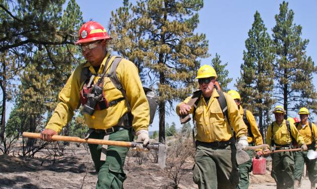 Tanilo Gonzalez leads his crew from G.H. Ranch down a road near Sprague River, Ore. on Monday, July 14, 2014. Fire spokeswoman Erica Hupp said Tuesday, July 15, 2014 the flames began moving Monday, burning a swath half the length of a football field in an area where containment lines hadn't been dug. (AP Photo/Herald And News, Dave Martinez)