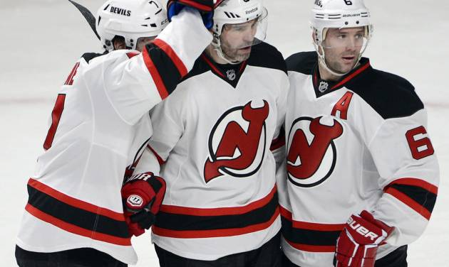 New Jersey Devils right wing Jaromir Jagr (68) celebrates with teammates Mark Fayne, left, and Andy Greene, right, after scoring the first goal against the Montreal Canadiens during first period National Hockey League action, Tuesday, Jan. 14, 2014, in Montreal. (AP Photo/The Canadian Press, Ryan Remiorz)