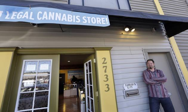 Cannabis City owner James Lathrop briefly leans against the exterior of his new recreational marijuana store Monday, July 7, 2014, in Seattle. The shop will be the first and, initially, only store in Seattle to legally sell recreational pot when sales begin Tuesday. (AP Photo/Elaine Thompson)