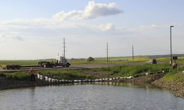 In this Monday, July 7, 2014 photo, cleanup workers deploy booms along the edge of a small reservoir at the site of a saltwater disposal facility that was struck by a lightning strike near Alexander, N.D. The strike at the facility sparked a fire and the release of 2,813 barrels of saltwater and 649 barrels of oil.  (AP Photo/Josh Wood)