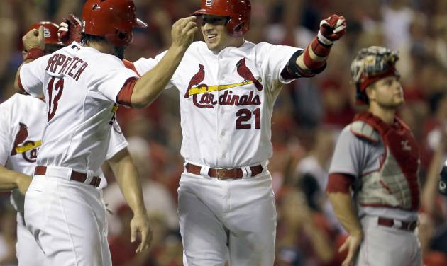 St. Louis Cardinals' Allen Craig, center, is congratulated by Matt Carpenter, left, after hitting a grand slam as Cincinnati Reds catcher Devin Mesoraco, right, stands by during the seventh inning of a baseball game, Monday, Aug. 26, 2013, in St. Louis. (AP Photo/Jeff Roberson)