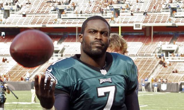 Philadelphia Eagles quarterback Michael Vick tosses a ball to a fan after a 17-16 win over the Cleveland Browns in an NFL football game on Sunday, Sept. 9, 2012, in Cleveland. (AP Photo/Ron Schwane)