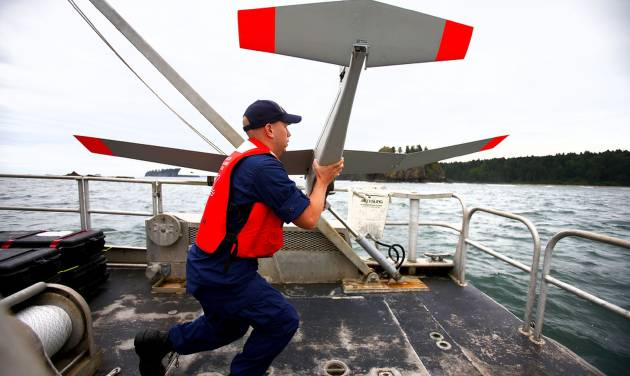 FILE - In this June 28, 2013 file photo, Nick Morgan, with the National Oceanic and Atmospheric Administration, prepares to launch a PUMA drone into the wind on the stern of the Research Vessel Tatoosh during a research mission near the Quillayute Needles Archipelago off the coast of La Push. Federal regulators say they have certified two types of unmanned aircraft for civilian use, a milestone expected to lead to the first approved commercial drone operations later this summer. The Federal Aviation Administration said Friday the drones are Insitu's Scan Eagle X200 and AeroVironment's PUMA. Both weigh less than 55 pounds, are about 4.5 feet long and have wingspans of 9 to 10 feet. (AP Photo/The Seattle Times, John Lok) OUTS: SEATTLE OUT, USA TODAY OUT, MAGAZINES OUT, TELEVISION OUT, SALES OUT. MANDATORY CREDIT TO:JOHN LOK/THE SEATTLE TIMES