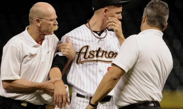 Houston Astros trainers help relief pitcher Mickey Storey, center, off the field after he was hit by a line drive from Chicago Cubs' Dave Sappelt in the eighth inning of a baseball game Wednesday, Sept. 12, 2012, in Houston. (AP Photo/Pat Sullivan)