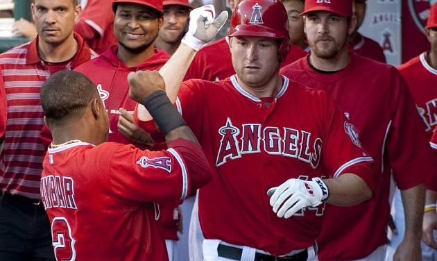 Los Angeles Angels left fielder Mark Trumbo celebrates with shortstop Erick Aybar, left, after Trumbo's solo home run against the Seattle Mariners in the second inning of a baseball game in Anaheim, Calif., Tuesday, June 5, 2012. (AP Photo/Grant Hindsley)