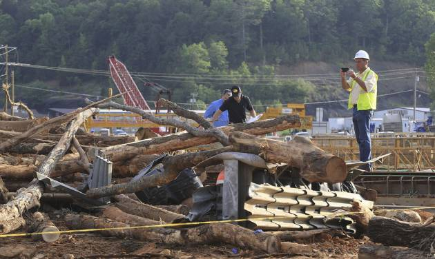 Investigators look over the scene of a double fatality accident Monday, June 2, 2014, in Clinton, Ark. Officials said a log truck lost control and slid onto a bridge under construction killing two and injuring more than 20 workers on the bridge. (AP Photo/Arkansas Democrat-Gazette, Staton Breidenthal)