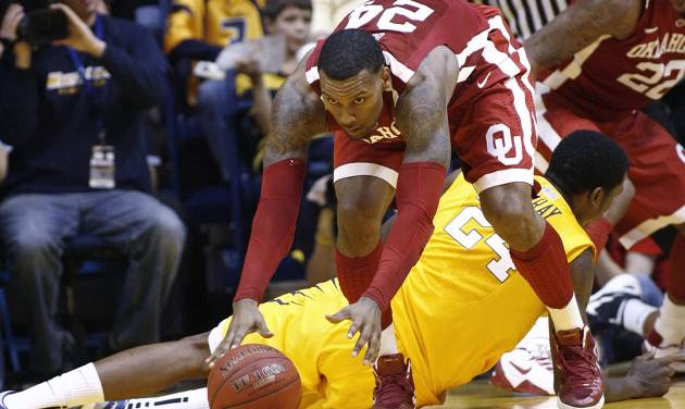 Oklahoma's Romero Osby gets by West Virginia's Aaric Murray, lying on floor, for a loose ball on Saturday, Jan. 5, 2013, during the second half of an NCAA college basketball game in Morgantown, W.Va. Osby led Oklahoma with 21 points in a 67-57 win. (AP Photo/Randy Snyder) ORG XMIT: WVRS109