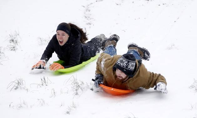 Austin Carter, right, sled races Isabelle Pommier down the hills in Avent  Park, Friday in Oxford, Miss., Jan. 22, 2016. The two Mississippi students took advantage of the university being closed to sled on the hills along with several dozen people. The two inches of accumulated power was enough for many families who trekked to the park to take advantage of the long gentle slopes for their children to slide down. Although the snow ceased falling, temperatures are expected to drop in the afternoon making for hazardous driving in north Mississippi. (AP Photo/Rogelio V. Solis)