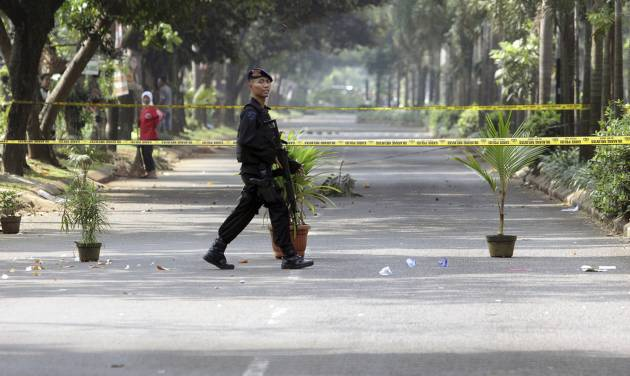 An armed paramilitary police guards the site where a police officer was shot and killed in Tangerang on the outskirts of Jakarta, Indonesia, Saturday, Aug. 17, 2013. Unidentified gunmen killed two police officers near Indonesia's capital, days after security forces made multiple arrests and killed suspects in anti-terrorism raids, police said Saturday. (AP Photo)