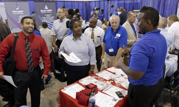 In this photo taken Wednesday, July 16, 2014, job seekers check out the opportunities at a Hiring Fair For Veterans in Fort Lauderdale, Fla. The Labor Department reports on the number of people who applied for unemployment benefits last week on Thursday, Aug. 7, 2014. (AP Photo/Alan Diaz)