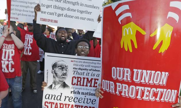 Hundreds of workers, organizers, and supporters gather outside of the McDonald's Corporation Thursday, May 22, 2014, in Oak Brook, Ill., protesting for a $15 an hour wage and the right to unionize. The group gathered outside the entrance as the company held the annual shareholders meeting. (AP Photo/M. Spencer Green)
