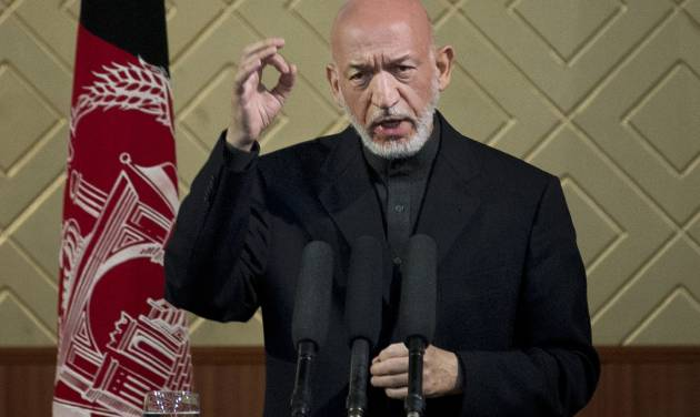 """Afghan President Hamid Karzai gestures during a ceremony at Kabul University in Kabul, Afghanistan, Thursday, May 9, 2013. Karzai said he is ready to let the U.S. have nine bases in the country after the 2014 combat troop pullout, but wants Washington's """"security and economic guarantees"""" first.  (AP Photo/Anja Niedringhaus)"""