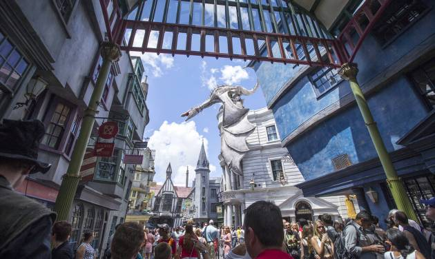 This image released by Universal Orlando shows guests at Diagon Alley at the Wizarding World of Harry Potter at Universal Orlando, in Orlando, Fla., on Wednesday, July 9, 2014. For a second day in a row, visitors waited up to five hours to get on the ride, Harry Potter and the Escape from Gringotts, located in the new Diagon Alley section of Universal Studios. On Tuesday, July 8, on the first day Diagon Alley was open to the public, visitors waited for as long as seven hours. (AP Photo/Universal Orlandi, Sheri Lowen)