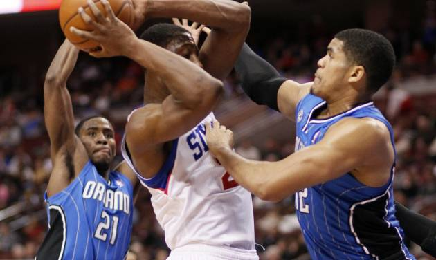 Philadelphia 76ers' Thaddeus Young, center, is blocked by Orlando Magic's Tobias Harris, right, during the second half of an NBA basketball game on Wednesday, Feb 26, 2014, in Philadelphia. (AP Photo/Tom Mihalek)