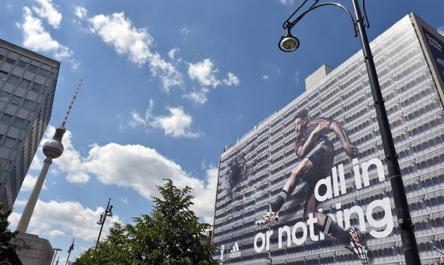 German national soccer player Mesut Ozil  is visible  on the facade of a publisher's building at Alexanderplatz  square in Berlin, Germany, Friday June 6, e 2014. Sportswear manufacturer Adidas has put up the advertisement on the entire facade of the building prior to the soccer World Cup  tournament  in Brazil. (AP Photo/dpa,Jens Kalaene)