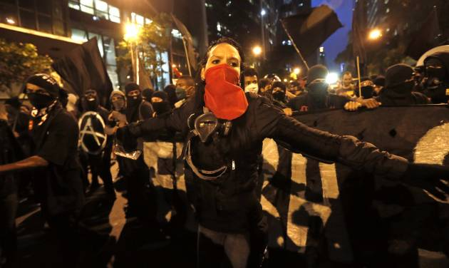 Masked members of the so-called Black Bloc anarchist group join in a march in support of striking teachers, marking National Teachers Day, in Rio de Janeiro, Brazil, Tuesday, Oct. 15, 2013. Teachers have been on strike demanding better pay for more than two months. Last week, a largely peaceful rally turned violent in Rio when small groups of masked protesters started hurling rocks and gasoline bombs at banks, stores and restaurants and set fire to a passenger bus. During the march Black Bloc anarchists tried to incite the crowd, but were kept in check by other demonstrators. (AP Photo/Silvia Izquierdo)