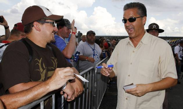 Kentucky men's basketball coach and honorary pace car driver John Calipari, right, signs autographs for fans before the NASCAR Sprint Cup auto race at Kentucky Speedway at Sparta, Ky., Saturday, June 29, 2013. (AP Photo/James Crisp)