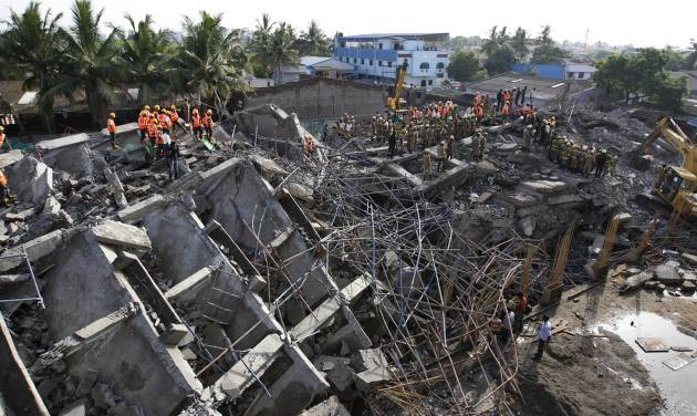 Rescuers search for workers believed buried in the rubble of a building that collapsed on the outskirts of Chennai, India, Sunday, June 29, 2014. Police said dozens of workers have been pulled out so far and the search is continuing. (AP Photo/Arun Sankar K)