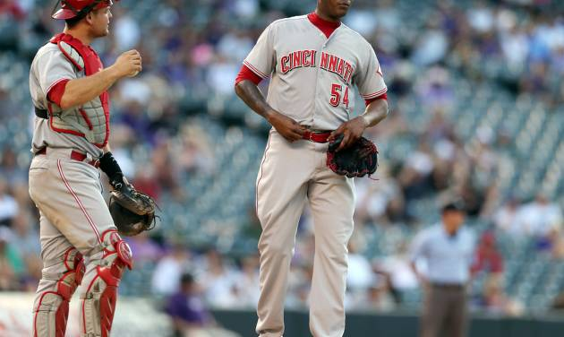 Cincinnati Reds catcher Devin Mesoraco, left, talks with relief pitcher Aroldis Chapman with the bases loaded against in the ninth inning of a baseball game against the  the Colorado Rockies in Denver on Sunday, Aug. 17, 2014. The Rockies won 10-9. (AP Photo/David Zalubowski)