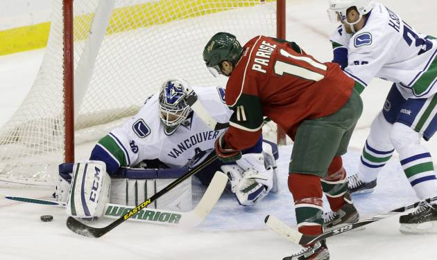 CORRECTS TO CANUCKS GOALIE CORY SCHNEIDER NOT ROBERTO LUONGO - Vancouver Canucks goalie Cory Schneider, left, stops a shot by Minnesota Wild's Zach Parise (11) as Vancouver Canucks' Henrik Sedin, right, of Sweden, helps defend the net in the first period of an NHL hockey game on Thursday, Feb. 7, 2013, in St. Paul, Minn. (AP Photo/Jim Mone)