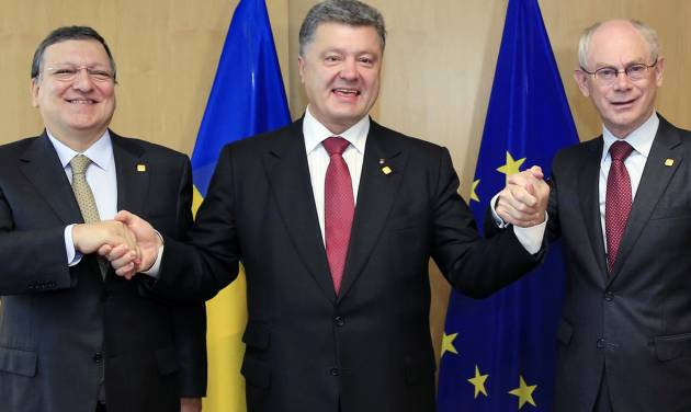"""Ukraine's President Petro Poroshenko, center, poses with European Commission President Jose Manuel Barroso, left, and European Council President Herman Van Rompuy, right, during an EU Summit in Brussels on Friday, June 27, 2014. Ukrainian President Petro Poroshenko has signed up to a trade and economic pact with the European Union, saying it may be the """"most important day"""" for his country since it became independent from the Soviet Union. (AP Photo)"""