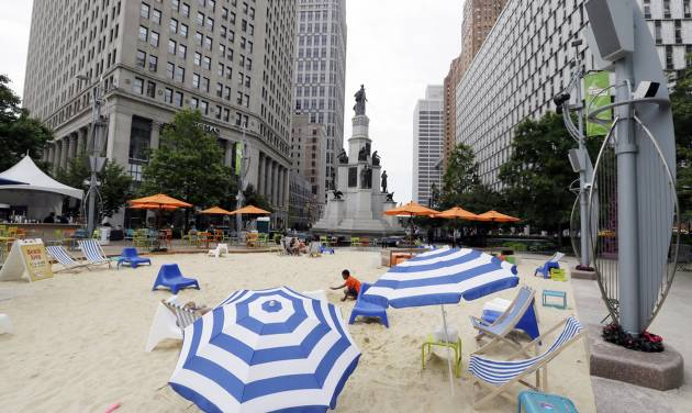 In this June 23, 2014, photo, a beach scene is displayed at Campus Martius in Detroit. Campus Martius is a 1.6-acre park where the historic Woodward and Michigan avenues converge. It opened in 2004 after several years of plans and more than $20 million in donations. (AP Photo/Carlos Osorio)