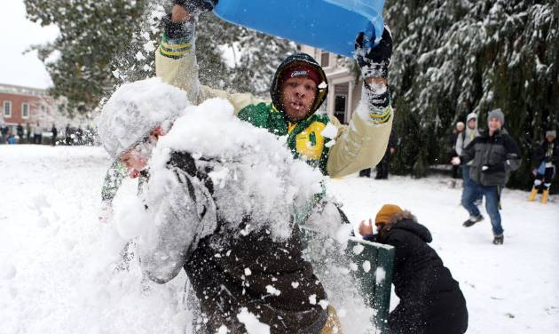 University of Oregon football player Pharaoh Brown, center, dumps a tub load of snow on fellow student Charley Gibson during a snow battle involving hundreds of students on campus Friday, Dec. 6, 2013. (AP Photo/The Register-Guard, Chris Pietsch)