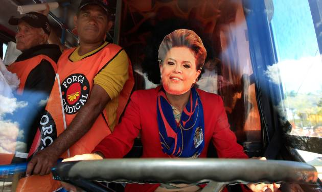 """A demonstrator, wearing a mask in the likeness of Brazil's President Dilma Rousseff, sits in the driver's seat of a bus during a protest in front of the Planalto presidential palace in Brasilia, Brazil, Thursday, July 11, 2013.  Workers across Brazil walked off their jobs on Thursday in a peaceful nationwide strike demanding better working conditions and improved public services. Metalworkers, transportation and construction workers as well as teachers and civil servants adhered to the """"Day of Struggle"""" organized by Brazil's biggest trade union federations. (AP Photo/Eraldo Peres)"""
