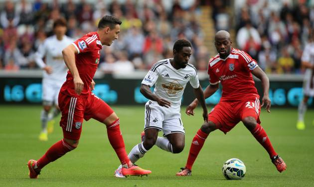 Swansea City's Nathan Dyer, center, skips over tackles from West Bromwich Albion's Youssuf Mulumbu, right, and Jason Davidson during their English Premier League soccer match at the Liberty Stadium, Swansea, Wales, Saturday, Aug. 30, 2014. (AP Photo/Nick Potts, PA Wire)    UNITED KINGDOM OUT   -   NO SALES   -   NO ARCHIVES