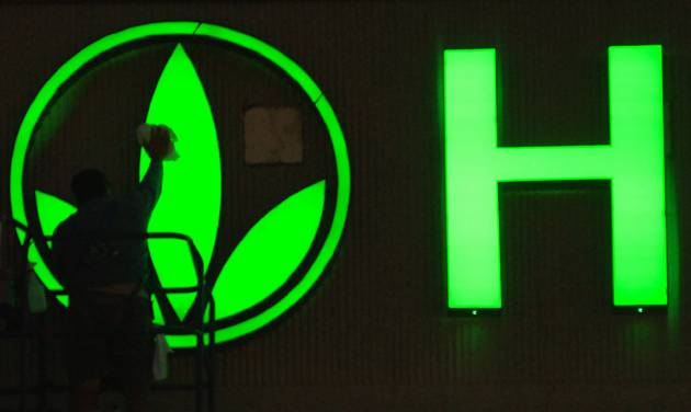 FILE- In this Friday, Sept. 8, 2006, file photo, a worker cleans the logo on the Herbalife sign as finishing touches are put on the company's building in Torrance, Calif. Herbalife came out swinging Thursday, Jan. 10, 2013 against claims made by hedge fund manager William Ackman that the business amounts to a pyramid scheme. (AP Photo/Herbalife, Susan Goldman)