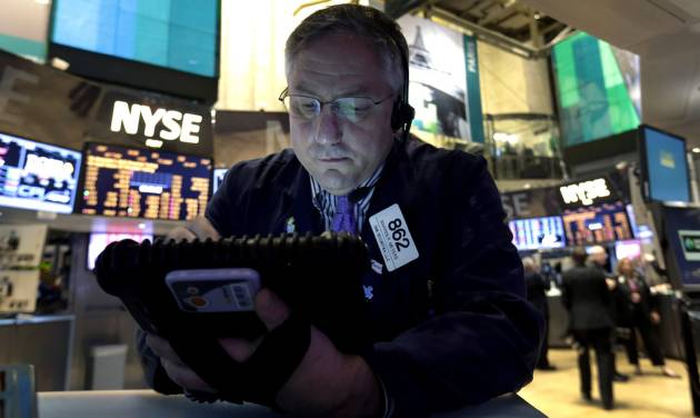 FILE - In this New York Stock Exchange Friday, Dec. 21, 2012, photo, Trader Warren Meyers uses his handheld device as he works on the floor of the New York Stock Exchange. Stocks are down Monday, Dec. 24, 2012, amid concern that lawmakers will fail to reach a deal to stop the U.S. going over the so-called fiscal cliff. (AP Photo/Richard Drew)