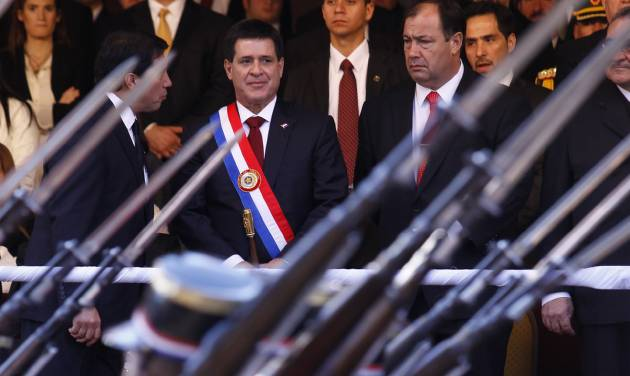 In this Aug.15, 2013 photo, Paraguay's President Horacio Cartes, center, and Vice President Juan Afara, right, attend a military parade in Asuncion, Paraguay. Cartes wants open-ended, blanket approval to send troops to the northern department of San Pedro against the Paraguayan People's Army without having to declare a state of emergency. The government blames the guerrilla group for the recent deaths of five farmhands. Human rights groups fear the step, but Cartes has plenty of support. House approval was expected Wednesday night, Aug. 21, 2013, before a Senate vote Thursday afternoon. (AP Photo/ Cesar Olmedo)