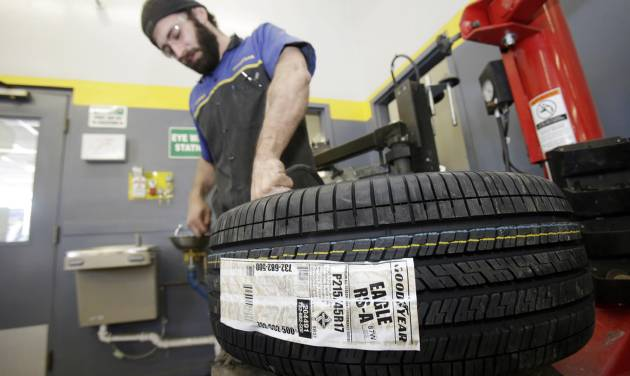 In this Feb. 12, 2014 photo, Lonn Schubert installs a Goodyear tire on a rim in South Euclid, Ohio. Goodyear reports quarterly earnings on Tuesday, April 29, 2014.  (AP Photo/Tony Dejak)