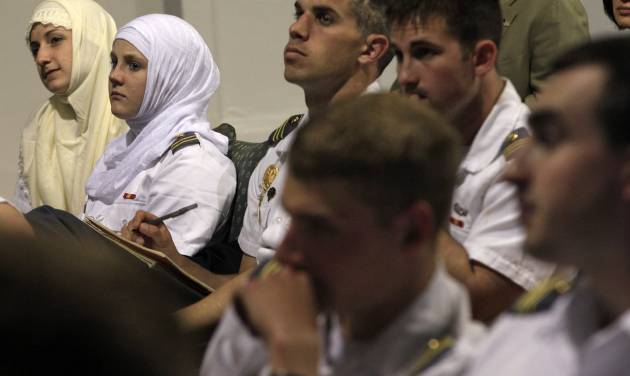 "Senior Megan Kelty, left, and junior Jordan Reilly, second left, wear Muslim headscarves out of respect, as they sit with other cadets from the U.S. Military Academy at West Point, N.Y., during a presentation at the Islamic Center of Jersey City Thursday, April 26, 2012, in Jersey City, N.J. The city of 250,000 is one of the most ethnically and religiously diverse places in America, and the cadets are visiting as part of a class at West Point on peacekeeping and reconstruction called ""Winning the Peace."" The class ends in a three-day crash course designed to make the future officers _ and, ultimately, the soldiers under their command _ more sensitive to cultural differences. (AP Photo/Mel Evans)"