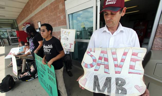 "Ardian Zoto, right, an employee of Market Basket for six years, holds a sign outside the supermarket in Danvers, Mass., Monday, Aug. 4, 2014. Executives at the troubled Market Basket supermarket chain in New England say they have heard from employees who are ""concerned for their safety"" in a dispute over the company's direction. In a statement Monday, co-CEOs Felicia Thornton and Jim Gooch say the employees are worried about attending a job fair that was set up to replace colleagues who walked off the job to protest the firing of the previous CEO. (AP Photo/Elise Amendola)"