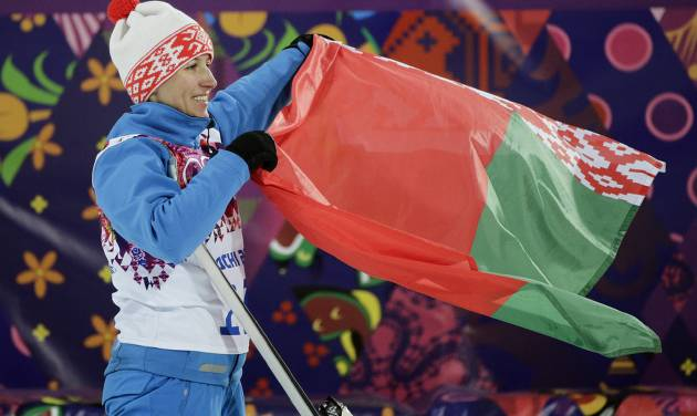 Gold medalist Alla Tsuper, of Belarus, poses with a Belarusian flag after a flower ceremony for the women's freestyle skiing aerials final at the Rosa Khutor Extreme Park, at the 2014 Winter Olympics, Friday, Feb. 14, 2014, in Krasnaya Polyana, Russia. (AP Photo/Jae C. Hong)