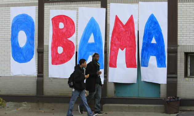 Jaylen Williams, left, and Sean Tyus walk past a homemade Obama sign on their way to school, Wednesday, Nov. 7, 2012, in the Over-the-Rhine neighborhood of downtown Cincinnati. President Barack Obama captured a second White House term on Tuesday over the challenge by Republican Mitt Romney. (AP Photo/Al Behrman)