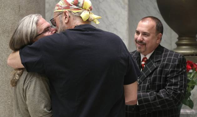 Pastor Randy Eddy-McCain, right, concludes a wedding ceremony at the Pulaski County Courthouse in Little Rock, Ark., for a same-sex couple who did not wish their names used Thursday, May 15, 2014. Marriage licenses were issued to same-sex couples in the county Thursday. (AP Photo/Danny Johnston)