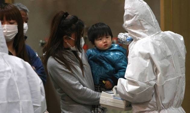 FILE - In this March 15, 2011 file photo, a child is screened for radiation exposure at a testing center in Koriyama city, Fukushima Prefecture, Japan, after a nuclear power plant on the coast of the prefecture was damaged by March 11 earthquake. Experts and the government say there have been no visible health effects from the radioactive contamination from Fukushima Dai-ichi so far. But they also warn that even low-dose radiation carries some risk of cancer and other diseases, and exposure should be avoided as much as possible, especially the intake of contaminated food and water. Such risks are several times higher for children and even higher for fetuses, and may not appear for years. Okinawa has welcomed the people from Fukushima and other northeastern prefectures (states) affected by the March 11, 2011, earthquake and tsunami that set off the nuclear disaster. (AP Photo/Wally Santana,File)