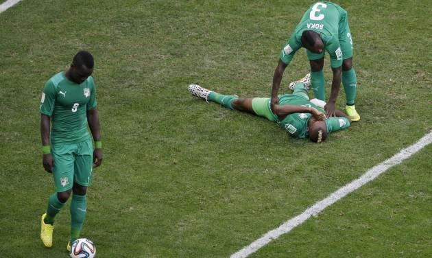 Ivory Coast's Serey Die is comforted by Arthur Boka after Colombia scored the second goal during the group C World Cup soccer match between Colombia and Ivory Coast at the Estadio Nacional in Brasilia, Brazil, Thursday, June 19, 2014.  At left Ivory Coast's Arthur Boka. Colombia won 2-1.(AP Photo/Themba Hadebe)