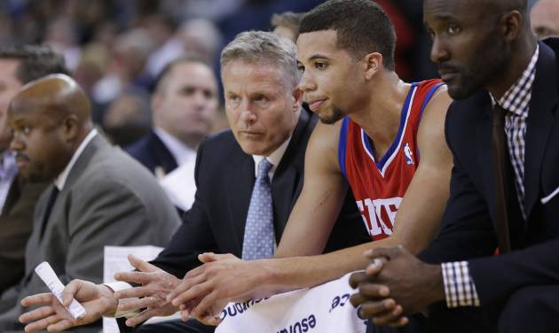 Philadelphia 76ers head coach Brett Brown, left, talks to point guard Michael Carter-Williams, center, in the closing minutes of a 123-80 loss to the Golden State Warriors during the second half of an NBA basketball game on Monday, Feb. 10, 2014, in Oakland, Calif. (AP Photo/Marcio Jose Sanchez)