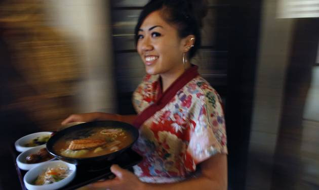 In this April 4, 2014 photo, food server Kathy Nguyen delivers a traditional Japanese meal to a customer at Domo, in Denver. Owner and head chef Gaku Homma has shaped Domo into a place where you can immerse yourself in Japanese culture, by visiting a museum that evokes a northern Japanese farmhouse, strolling in a garden studded with Buddha statues, or even taking a martial arts class in the converted former warehouse where the restaurant compound is located. Homma uses the profits not to enrich himself financially, but instead funds orphanages around thew world. (AP Photo/Brennan Linsley)