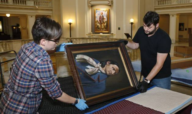 "Kristi Wyatt, left,  and Brad Stevens, of the Fred Jones Jr. Museum of Art at the University of Oklahoma, prepare artwork for shipping to Oklahoma State University's museum of art, at the state Capitol in Oklahoma City, Tuesday, June 10, 2014. The painting they are packing is titled ""Chief Peter Pitchlynn"". Museum officials from the state's two flagship universities are packing 55 separate pieces of art from the Oklahoma Senate collection to ship to Stillwater for display in a new university museum. (AP Photo/Sue Ogrocki)"