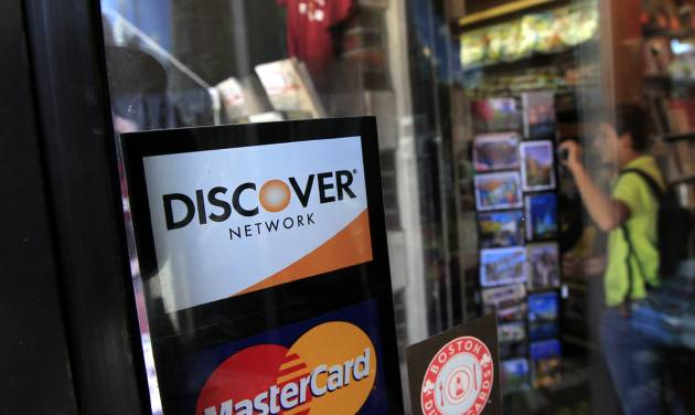 FILE - This Monday, Sept. 24, 2012, file photo shows a Discover logo in the window at the entrance of a shop in Cambridge, Mass. Discover Financial reported quarterly financial results on Tuesday, July 22, 2014. (AP Photo/Steven Senne, File)
