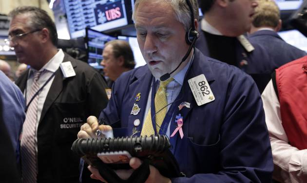 FILE - In this Wednesday, Dec. 18, 2013, file photo, trader Warren Meyers, center, works on the floor of the New York Stock Exchange. Investors continued Friday, Dec. 20, 2013 to breathe a sigh of relief that the U.S. central bank has committed to keeping interest rates low even though it has decided to start pulling back on its monetary stimulus. (AP Photo/Richard Drew, File)
