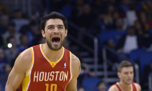 Houston Rockets' Carlos Delfino (10) celebrates after scoring a three-point basket as teammate Chandler Parsons runs upcourt during the first half of an NBA basketball game against the Orlando Magic in Orlando, Fla., Friday, March 1, 2013. (AP Photo/Phelan M. Ebenhack)